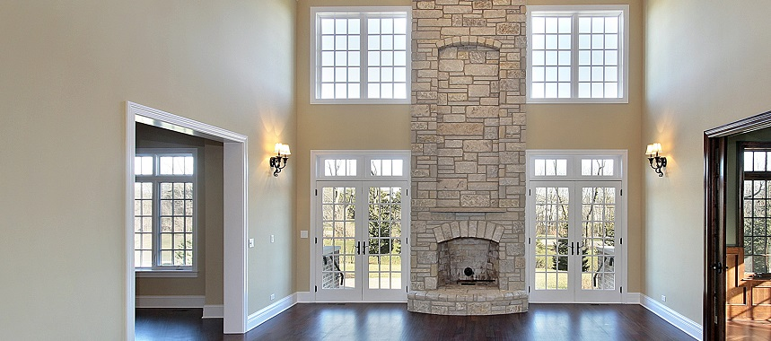 Family room in new construction home with two story stone fireplace